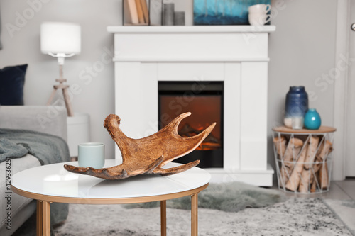 Wallpaper Mural Moose antler on table in interior of room with fireplace