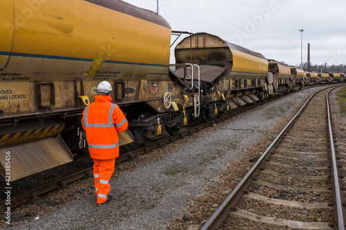 Canvas Print A railway worker walking and inspecting a Network Rail goods train for HS2