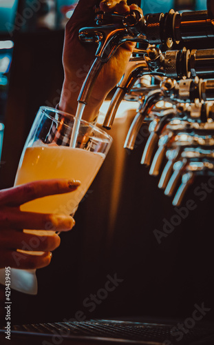 Canvastavla bartender hand at beer tap pouring a draught beer in glass serving in a restaura
