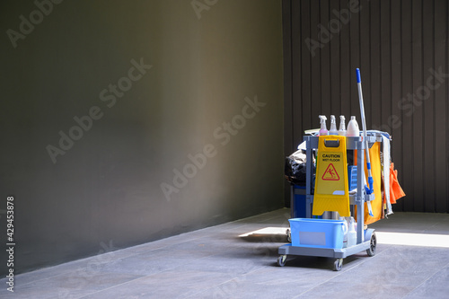Fotomural Janitor carts with cleaning equipment for the housekeeper with the slippery caution sign