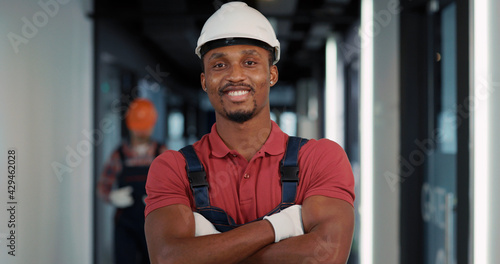 Valokuva African american engineer in protective helmet and uniform posing confident for camera inside construction building interior
