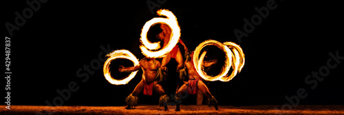 Canvas Luau hawaiian fire dancers motion blur tourist attraction in Hawaii or French Polynesia, traditional polynesian dance with men dancer