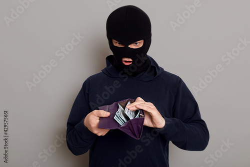 Photo Surprised man thief dressed in robber mask holding open wallet in his hands, shocked by what he sees, steals big sum of money, posing isolated over gray background