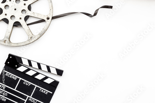 Cinema background with movie clapperboard and film reel Fototapet