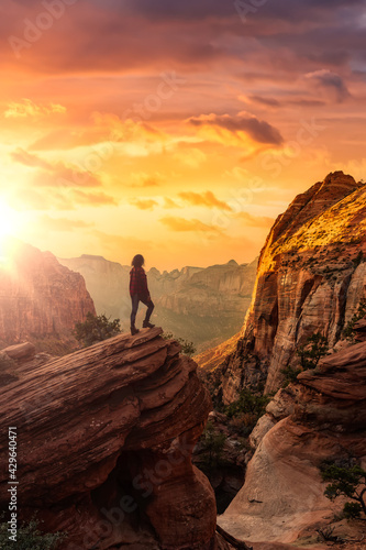 Adventurous Woman at the edge of a cliff is looking at a beautiful landscape view in the Canyon Fotobehang