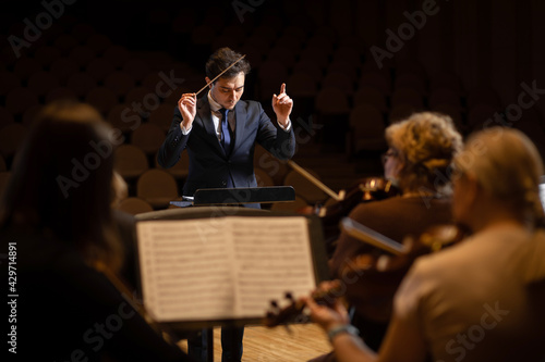 Stampa su Tela Conductor of symphony orchestra with performers in background in concert hall