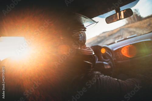Obraz na plátně Rally racer in a helmet is driving a car concept.