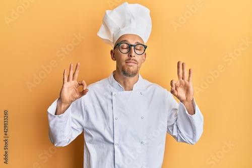 Obraz na plátně Bald man with beard wearing professional cook uniform relax and smiling with eyes closed doing meditation gesture with fingers