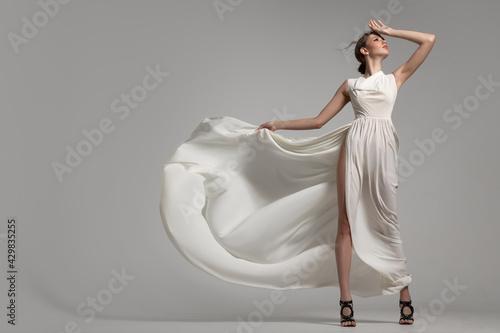 Fashion woman portrait in white long flying airy dress Fotobehang