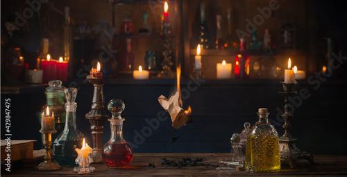 Obraz na plátně old burning paper with potions on old wooden table