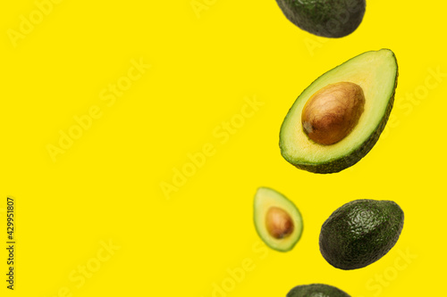 Cuadros en Lienzo pitted avocado and whole avocado fly in the air on a yellow background