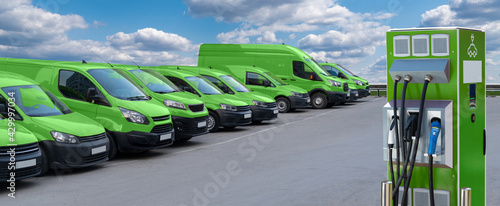 Electric vehicles charging station on a background of a row of vans. Green transportation concept