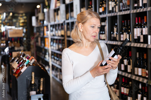 Photo Portrait of mature woman visiting winehouse in search of bottle of good wine