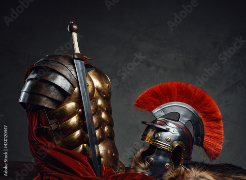 Fotografia, Obraz Armored clothing with helmet and sword against dark background