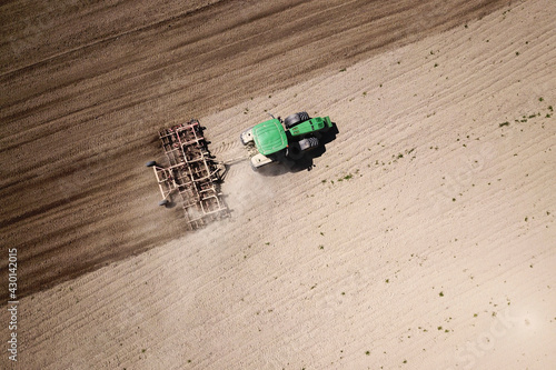 Fotografie, Obraz Top view of Green Tractor cultivates the field with liner