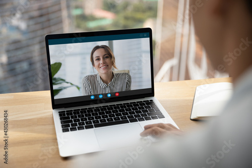 Canvas Rear over shoulder view of man talk speak with smiling female colleagues on video online call on laptop