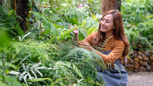 Fotografiet A young asian female gardener taking care of plants in the garden
