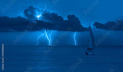 Fotografie, Obraz Sailing yacht in a stormy weather with thunder and lightning