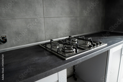 Slika na platnu Stainless grey metal kitchen gas stove installed on a the kitchen with a dark grey table top