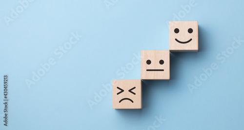 Slika na platnu Flipping of wooden cube block from sad to smile emotion on blue background