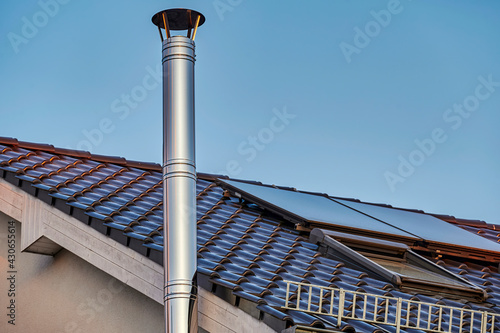Fotografia A stainless steel chimney and parts of a roof with solar panels at dusk