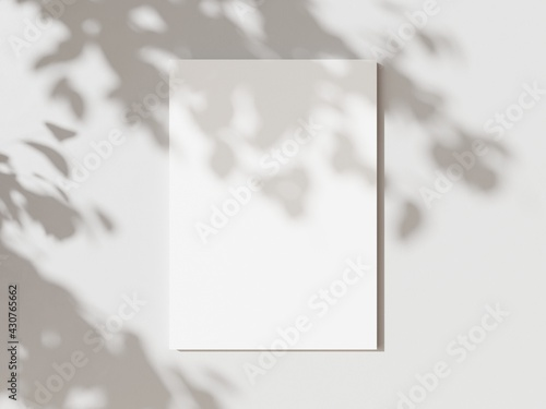 Fotografie, Obraz Empty white vertical rectangle poster mockup with soft hawthorn leaves shadows on neutral light grey concrete wall background