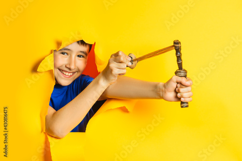 Canvas-taulu Boy holds a wooden slingshot ready to be shot charged with walnut breaking a torn hole in a paper yellow wall