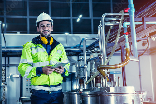 Happy engineer male worker working in factory using tablet computer to check boiler water pipe in factory, portrait smile Fototapet