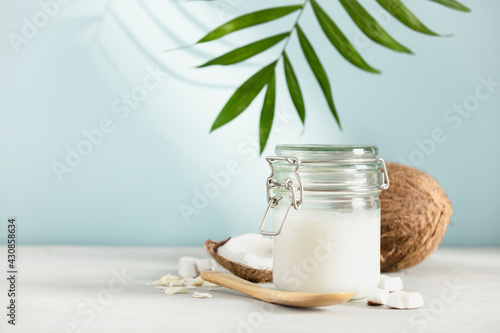 Coconut oil in jar with fresh coconut and tropical leaves, Spa cosmetic and food Fototapet