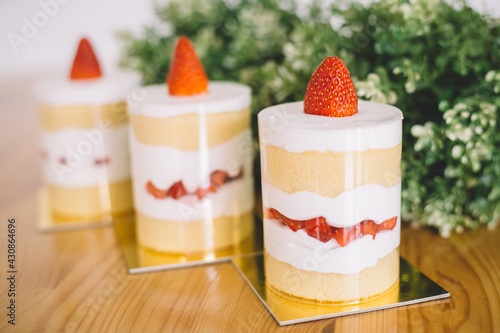 Fotografia, Obraz Strawberry shortcakes with whipped cream and fresh berries on wooden table