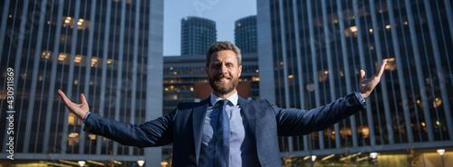 Photo Businessman raising arms near cityscape office building