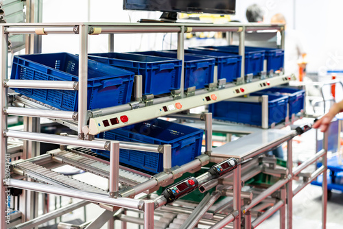 Obraz na płótnie basket or plastic box container on roller rack or aluminum shelf with electronic display smart module system for management – control or operate stock such as quantity and data information etc
