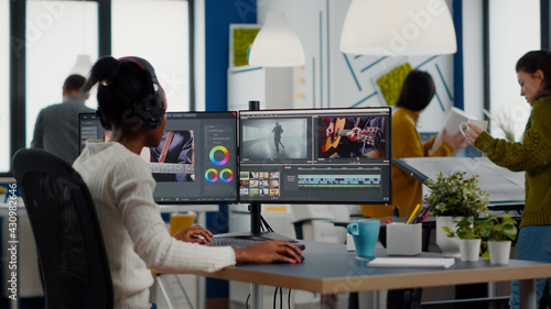 Black videographer putting on headset editing movie using post production software working in creative start up agency office. African editor processing video footage on computer with dual displays
