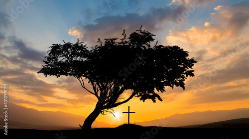 Fotografie, Obraz The view on the tomb cross on the beautiful sunset sky background