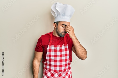 Obraz na plátně Young hispanic man wearing baker uniform tired rubbing nose and eyes feeling fatigue and headache