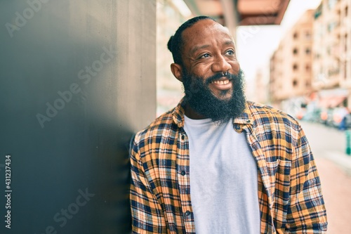 Fototapeta Handsome modern african american man with beard smiling positive leaning over wa