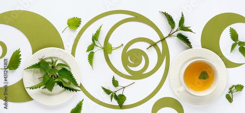 Mata na ścianę w kuchni  baner-filizanka-herbaty-pokrzywy-liscie-ziol-pokrzywy-kwiecisty-plasko-swieckich-zielone-kola-sekwencji-fibonacciego-off-biale-tlo-zdrowa-herbata-ziolowa-obraz-panoramiczny-medycyna-alternatywna-lek-ziolowy