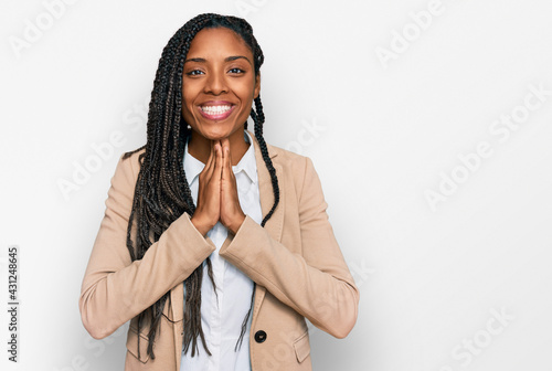 Valokuvatapetti African american woman wearing business jacket praying with hands together asking for forgiveness smiling confident