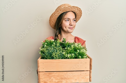 Beautiful brunette little girl wearing gardener hat holding wooden plant pot smiling looking to the side and staring away thinking Fototapet
