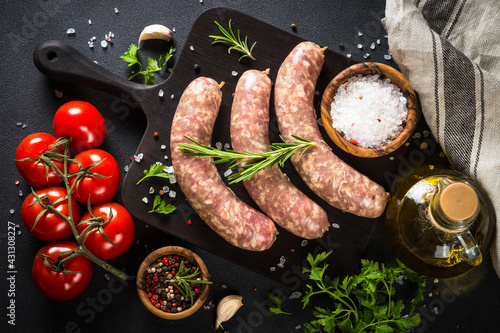 Canvas Print Bratwurst or sausages on cutting board with spices at black table