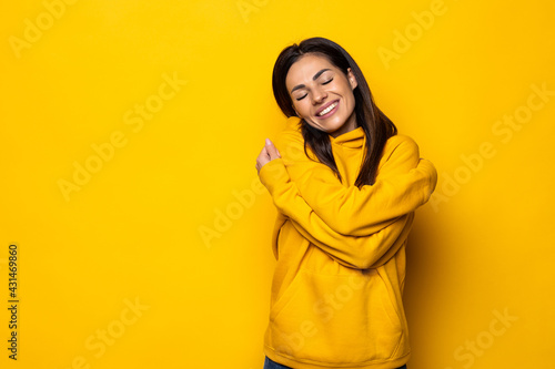 Wallpaper Mural Young business woman hugs herself, smiling carefree and happy.