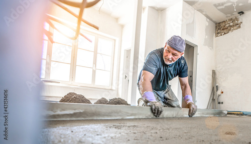 Fotografie, Obraz Filling the floor of a renovated apartment with concrete, screed and leveling the floor by construction workers