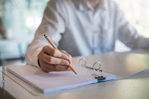 Fotografia Close up of a woman holding a pencil taking notes at the office.