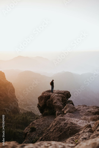 Foto Man with a backpack standing on top of a cliff during the sunset