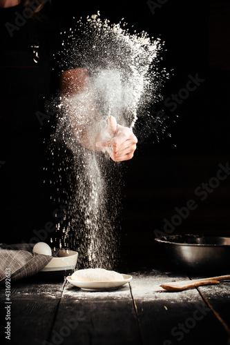 Fotografie, Obraz Baker hands sprinkling with flour pizza preparation