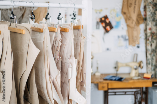 Fotografia, Obraz Many paper sewing patterns for different clothes hanging on the rack in sewing factory background
