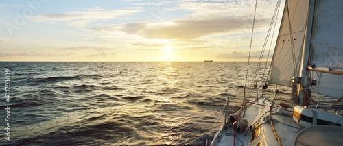 Fotografia White sailboat in an open sea at sunset
