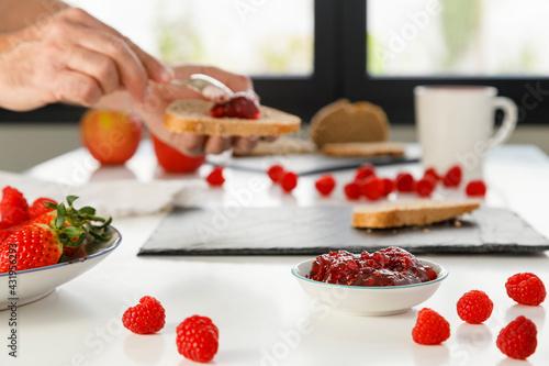 Fototapete Hands of man preparing breakfast with raspberry jam