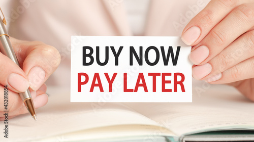 a card in the hands of a businesswoman with the inscription buy now pay later