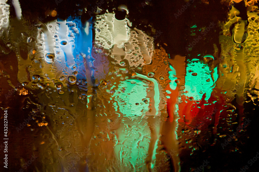 Abstract views of patterns and colors on a car windshield during a rainstorm in a city at night.